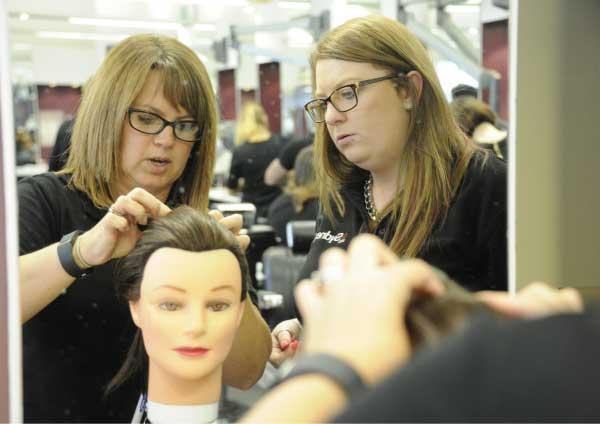 A hairdressing tutor and student practising on a wig.